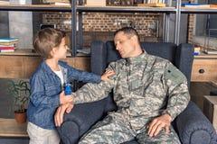 κουρασμένο άτομο στον ύπνο στρατιωτικών στολών στην πολυθρόνα με το γιο πλησίον στοκ εικόνα
