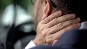 Κουρασμένο άτομο στο κοστούμι που αισθάνεται την ταλαιπωρία λαιμών, που οδηγεί το αυτοκίνητο, στατικός τρόπος ζωής στοκ φωτογραφίες
