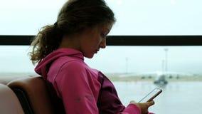 Κουρασμένο αθλητισμός smartphone χρήσεων γυναικών από το παράθυρο αερολιμένων Αεροπλάνο στο υπόβαθρο απόθεμα βίντεο