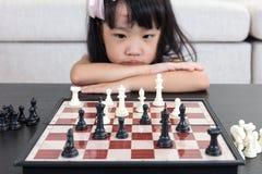 Κουρασμένο ασιατικό κινεζικό σκάκι παιχνιδιού μικρών κοριτσιών στο σπίτι στοκ εικόνα με δικαίωμα ελεύθερης χρήσης