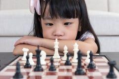 Κουρασμένο ασιατικό κινεζικό σκάκι παιχνιδιού μικρών κοριτσιών στο σπίτι στοκ εικόνα