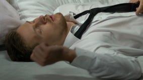 Κουρασμένο γυαλί κατανάλωσης επιχειρηματιών του οινοπνεύματος και πτώση κοιμισμένος στο κρεβάτι μετά από την εργασία φιλμ μικρού μήκους