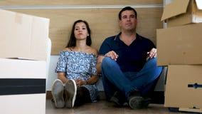 Κουρασμένο εξαντλημένο ζεύγος στο νέο σπίτι τους που χαλαρώνει μετά από να κινήσει όλα τα κουτιά από χαρτόνι μέσα φιλμ μικρού μήκους