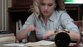 Κουρασμένο θηλυκό που παίρνει ένα NAP σε έναν σωρό των βιβλίων και που ξυπνιέται από έναν συναγερμό απόθεμα βίντεο