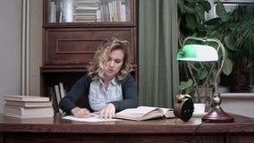 Κουρασμένο θηλυκό που παίρνει ένα NAP στο σωρό των βιβλίων στον εργασιακό χώρο της και που ξυπνιέται από έναν συναγερμό φιλμ μικρού μήκους