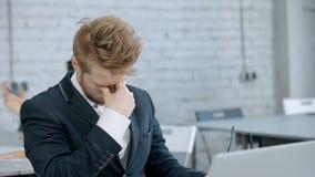Κουρασμένο και εξαντλημένο πρόσωπο που εργάζεται στο σύγχρονο γραφείο απόθεμα βίντεο