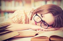 Κουρασμένο κορίτσι σπουδαστών με τα γυαλιά που κοιμούνται στα βιβλία στη βιβλιοθήκη Στοκ Εικόνες