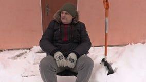 Κουρασμένο με ειδικές ανάγκες άτομο στην αναπηρική καρέκλα με το φτυάρι χιονιού φιλμ μικρού μήκους
