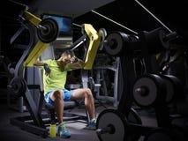 Κουρασμένο νέο bodybuilder που κάνει το βάρος που ανυψώνει στη γυμναστική Στοκ Φωτογραφία