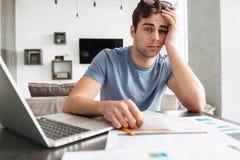 Κουρασμένο πολυάσχολο άτομο που φαίνεται κάμερα εργαζόμενο στο σπίτι Στοκ φωτογραφία με δικαίωμα ελεύθερης χρήσης