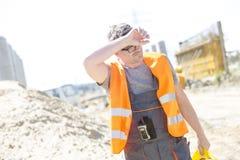 Κουρασμένο σκουπίζοντας μέτωπο εργατών οικοδομών επί του τόπου στοκ εικόνες