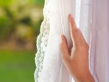 Κουρτίνες ανοίγματος χεριών γυναικών ` s στην κρεβατοκάμαρα με το φυσικό φως στοκ εικόνα