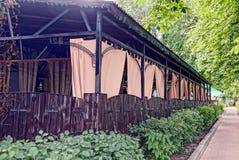 Κουρτίνες του ανοικτό καφέ χρώματος στα θερινά δωμάτια του εστιατορίου πίσω από έναν ξύλινο φράκτη Στοκ φωτογραφία με δικαίωμα ελεύθερης χρήσης