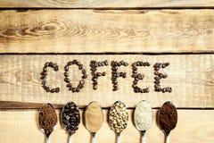 Κουτάλια με τον καφέ και μια επιγραφή σε έναν παλαιό ξύλινο πίνακα στοκ φωτογραφίες