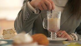 Κουτάλι εκμετάλλευσης χεριών γυναικών και καφές ανακατώματος latte στον πίνακα με το γλυκό κέικ απόθεμα βίντεο