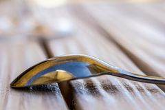 Κουτάλι καφέ με την αντανάκλαση της ομπρέλας παραλιών στον άσπρο πίνακα Στοκ Εικόνες