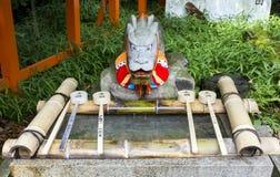 Κουτάλες καθαρισμού και ένα άγαλμα δράκων στη λάρνακα shinto στη Ja Στοκ Φωτογραφία