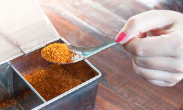 Κουτάλι εκμετάλλευσης γυναικών χεριών του πιπεριού του Cayenne με το πιπέρι του Cayenne σε ξύλινο Στοκ φωτογραφία με δικαίωμα ελεύθερης χρήσης
