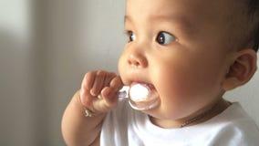 Κουτάλι εκμετάλλευσης μωρών στο στόμα και το κοίταγμα έξω Εύθυμο και καλό παιδί απόθεμα βίντεο