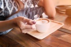 Κουτάλι εκμετάλλευσης χεριών γυναικών με τον καφέ latte Στοκ εικόνα με δικαίωμα ελεύθερης χρήσης