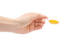 Κουτάλι εκμετάλλευσης χεριών γυναικών με το σιρόπι Στοκ Εικόνα