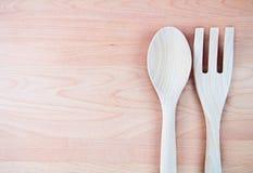 Κουτάλι και δίκρανο με το ξύλινο υπόβαθρο στοκ εικόνες