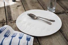 Κουτάλι και δίκρανο στο άσπρο πιάτο γευμάτων με το χαραγμένο σχέδιο δικράνων Στοκ εικόνα με δικαίωμα ελεύθερης χρήσης