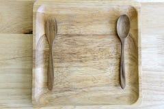 Κουτάλι και πιάτο δικράνων που γίνονται από το ξύλο στο ξύλινο υπόβαθρο στοκ εικόνες με δικαίωμα ελεύθερης χρήσης
