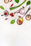 Κουτάλι με το έλαιο και τα καρυκεύματα και διάφορα χορτοφάγα συστατικά για την υγιή κατανάλωση στο άσπρο ξύλινο υπόβαθρο Στοκ Φωτογραφία