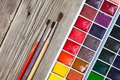 Κουτί χρωμάτων και τρεις βούρτσες σε μια κατασκευασμένη επιφάνεια Στοκ Εικόνα