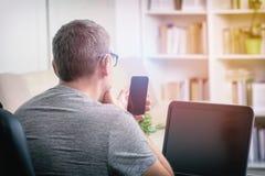 Κουφό άτομο που εργάζεται με το lap-top και το κινητό τηλέφωνο Στοκ Εικόνες