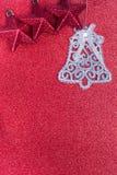 Κουδούνια Χριστουγέννων και κόκκινο αστέρι στο κόκκινο υπόβαθρο Στοκ εικόνα με δικαίωμα ελεύθερης χρήσης