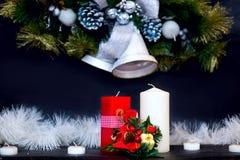 Κουδούνια Christmass, κόκκινα και άσπρα κεριά στο μαύρο υπόβαθρο Στοκ Εικόνα