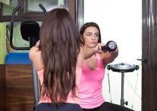 Κουδούνι κατσαρολών άσκησης μπροστινής άποψης δύο γυναικών Στοκ φωτογραφία με δικαίωμα ελεύθερης χρήσης