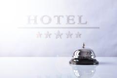 Κουδούνι υπηρεσιών στην υποδοχή ξενοδοχείων με το υπόβαθρο αφισσών ξενοδοχείων Στοκ Εικόνα