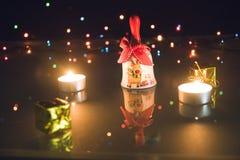 Κουδούνι Χριστουγέννων, μικρά δώρα και ελαφριά κεριά τσαγιού στο μαύρο backgound bokeh Στοκ φωτογραφία με δικαίωμα ελεύθερης χρήσης