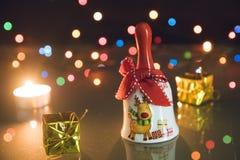 Κουδούνι Χριστουγέννων, μικρά δώρα και ελαφριά κεριά τσαγιού στο μαύρο backgound bokeh Στοκ Εικόνες