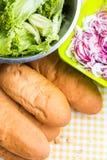Κουλούρια για τα χοτ-ντογκ με το μπέϊκον και το κρεμμύδι στο τραπεζομάντιλο Στοκ Εικόνες