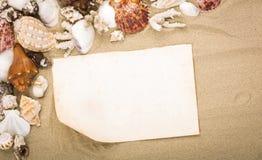 Κοχύλια θάλασσας στην άμμο παραλιών με το παλαιό έγγραφο Στοκ φωτογραφίες με δικαίωμα ελεύθερης χρήσης