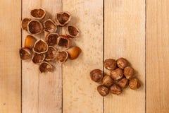 Κοχύλια των καρυδιών και των καρυδιών στον ξύλινο πίνακα Στοκ Φωτογραφίες