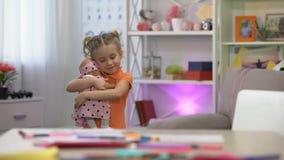 Κούκλα εκμετάλλευσης κοριτσιών, που αγκαλιάζει το αγαπημένο παιχνίδι, κοριτσίστικος ελεύθερος χρόνος, ευτυχία παιδικής ηλικίας φιλμ μικρού μήκους
