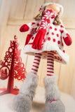 Κούκλα Χριστουγέννων και ένα κόκκινο χριστουγεννιάτικο δέντρο Στοκ φωτογραφία με δικαίωμα ελεύθερης χρήσης