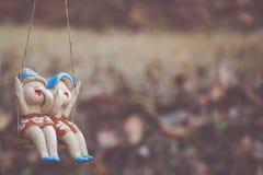 Κούκλες παιδιών αργίλου που κάθονται στην ταλάντευση στο σπίτι, έννοια της διακόσμησης Στοκ εικόνες με δικαίωμα ελεύθερης χρήσης