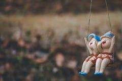 Κούκλες παιδιών αργίλου που κάθονται στην ταλάντευση στο σπίτι, την έννοια της διακόσμησης και τη ρύθμιση κήπων Στοκ φωτογραφίες με δικαίωμα ελεύθερης χρήσης