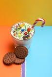 Κούνημα γάλακτος με τις ζωηρόχρωμα καραμέλες και τα μπισκότα Στοκ Εικόνες