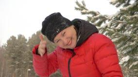 Κούνημα γυναικών χαμόγελου από το χιόνι από το χειμερινό περίπατο καπέλων χιονώδη δασικό σε σε αργή κίνηση φιλμ μικρού μήκους