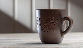 Κούπα αργίλου με τα σχέδια σε έναν άσπρο ξύλινο πίνακα, στις ακτίνες ήλιων πρωινού στοκ εικόνες