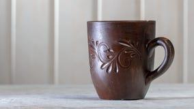 Κούπα αργίλου με τα σχέδια σε έναν άσπρο ξύλινο πίνακα, στις ακτίνες ήλιων πρωινού στοκ φωτογραφία