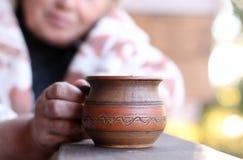 Κούπα αργίλου του τσαγιού ή του καφέ στα χέρια μιας ηλικιωμένης γυναίκας στο te στοκ φωτογραφία με δικαίωμα ελεύθερης χρήσης