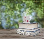Κούπα και βιβλία φλυτζανιών καφέ πέρα από τον ξύλινο πίνακα υπαίθρια, στο afternoo Στοκ Φωτογραφία